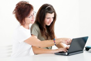 middle aged mother help teen daughter study
