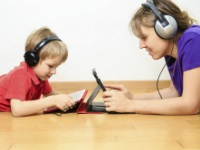 mother and son with headset looking at touch pad