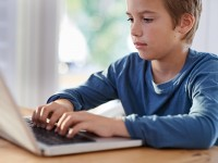 Shot of a young boy using a laptop at home